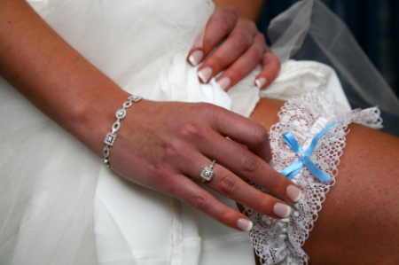 Bride putting garter on leg